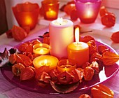 Pink glass plate with candles and wreath of Chinese lanterns