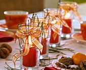 Red candles in drinking glasses with checked ribbons