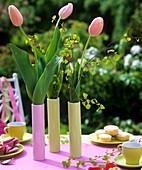Pink tulips on table laid for coffee in open air