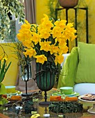 Table with daffodils, coffee cups and small cakes