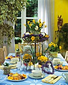 Table laid for Easter with flowers on tiered stand & bread ring