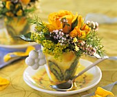 Cup with yellow roses, lady's mantle and thyme