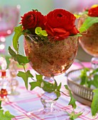 Red Ranunculus with ivy and sisal in wine glass