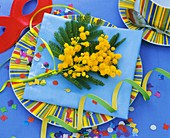 Mimosa on cake plate with confetti and paper streamers