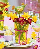Place-setting with Easter eggs, posy of narcissi and daisies