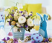 Easter arrangement with quail's eggs and felt hat as egg cosy