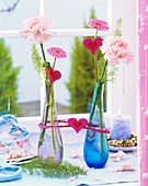 Carnations, Gerbera & ornamental asparagus in glass vases