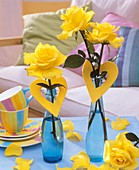 Yellow roses with foam rubber hearts in blue bottles
