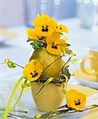 Yellow horned violets in golden egg vase with eggcup