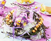 Easter nest of twigs, onions, horned violets and feathers