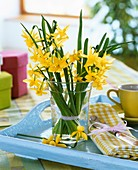 Narcissi in vase on tray with napkin and coffee cup