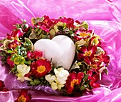 Heart in a wreath of primulas and hydrangea flowers