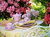 Rosa Geschirr, kleiner Streuselkuchen, Flieder & Rhododendron