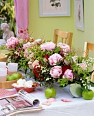 Peonies, lilies-of-the-valley, meringues, juice & apples on table