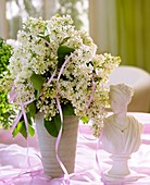 Vase of white lilac and female bust