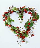 Strawberries with leaves and flowers forming a heart