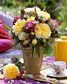 Vase of summer flowers on table laid for coffee outdoors