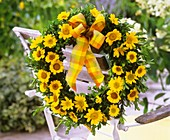 Wreath of golden marguerites and box hanging on chair back