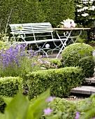 Garden seat and table in summery garden