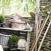 Garden tools and flowerpots by willow hurdle
