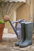 Rubber boots and watering can in front of garden tap