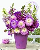 Arrangement of dahlias & other summer flowers in pink on garden table