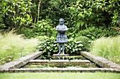 Stone figure by garden pond