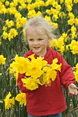 Blond girl holding bunch of daffodils