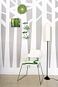 Wallpaper with tree design, chair, standard lamp