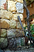 Wire hare figure by stone wall