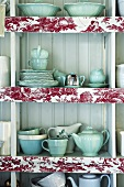 Open wall cabinet containing crockery