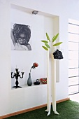 DIY coat rack in front of photograph on wall of niche