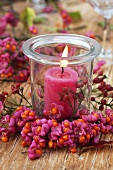 Candle in glass with wreath of spindle tree fruit