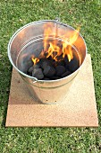 Barbecue bucket with burning charcoal