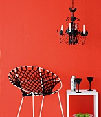 Macramé chair and small table against red wall