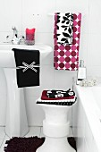 Various towels on stool and wash basin next to bathtub