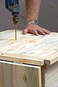 Mann bohrt Loch in eine Holzkiste