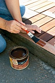 Woman painting wooden edging