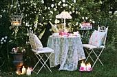 Abendlicher Tisch mit Stühlen im Rosengarten