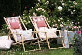 Two deckchairs with cushions in a rose garden