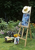 Easel with straw hat and picnic basket in a garden