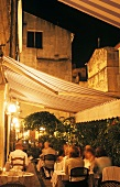 Terrace of a French restaurant in historic city setting at dusk