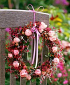 Wreath of roses and rose hips tied to a chair back