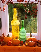Pumpkins, coloured bottles & rose hip branches at window