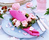 Festive place-setting with napkin ring of roses & rosemary