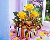 Arrangement of yellow roses, crab apples, apples & autumn leaves