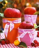 Apples on coloured beakers used as table decoration