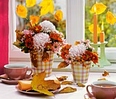 Vases of chrysanthemums and rose hips on tea table