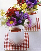 Posies of colourful meadow flowers in small milk cans