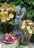 Garden decoration: roses, plate of fruit and stone figure